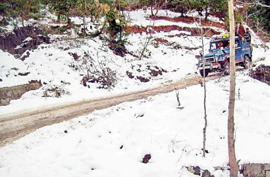 Abbotabad - a vehicle passes through snow covered Bakote Road on Thursday January 13 2011