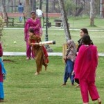 Women play cricket on the lawns of Rawal Lake View Park as the cricket fever