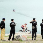 Pakistani policemen stand guard as local and international cyclists compete in the Himalayas 2011 International Mountainbike Race
